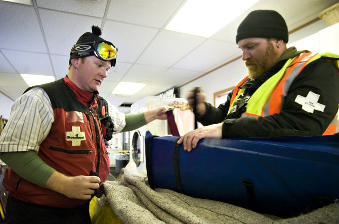 Ski patrollers Svend Egholm, left, and Scotty Sommerhoff wrap up a packet containing a backboard, blankets and splints to be used on rescue toboggans at the Steamboat Ski Area on Thursday afternoon.  Patrollers transport injured skiers and snowboarders down the mountain in the toboggans.