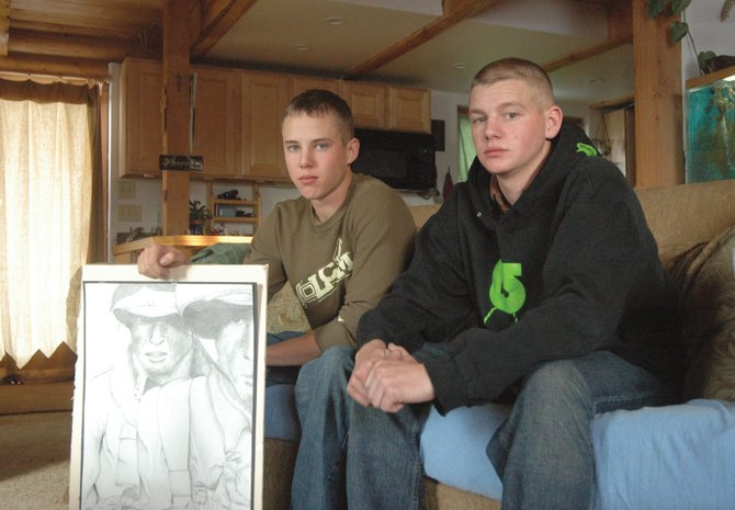 Pfc. Lucas Sullivan, left, holds his senior project, a drawing he completed before finishing Soroco High School a semester early to join the Marines. He and childhood friend Airman Ronald Nielsen, right, planned to enlist in the U.S. Armed Services before their 2007 high school graduations.