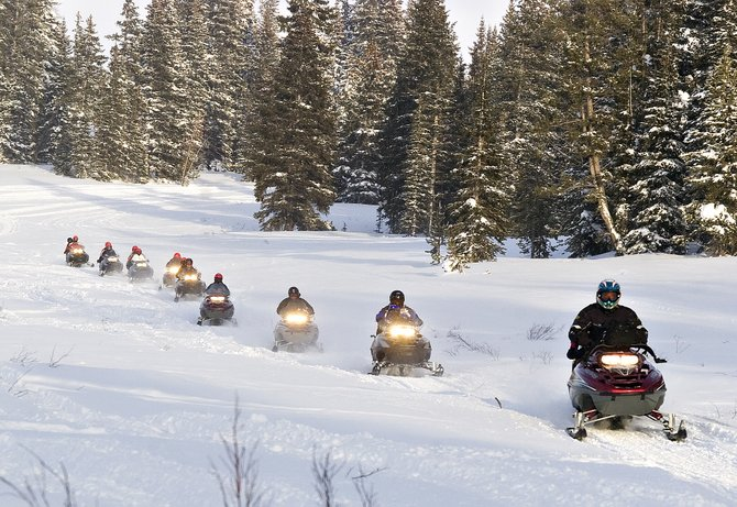 A commercial snowmobile tour operated by Steamboat Snowmobile Tours makes its way across a meadow on Rabbit Ears Pass near Steamboat Springs on Friday afternoon.