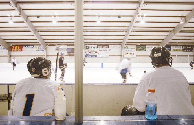 Jim Neton, left, and Lance Scranton take a break during the Craig Red Dogs hockey practice to watch a scrimmage Wednesday at the Moffat County Ice Arena.  The Red Dogs are one of 10 teams participating in the Yampa Valley Invite at the Moffat County Ice Arena. The tournament starts Friday, with the championship game Sunday.
