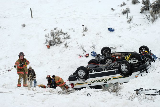 Emergency responders pull a victim from the scene of an accident Tuesday afternoon on the Colorado Highway 13 bypass, about a mile west of Colo. 13. A Jeep Liberty left the right side of the roadway and landed on its top in a ravine. Moffat County Sheriff's Office deputies responding to the scene then got into a similar accident. The Colorado State Patrol is investigating.