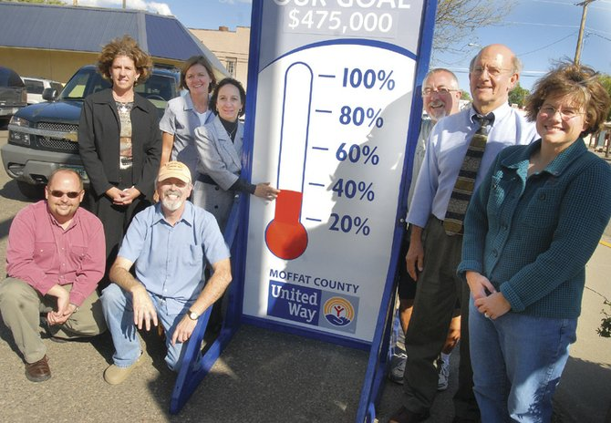 Representatives of the Moffat County United Way board and the Moffat County School District pose in front of the sign showing this year's United Way fundraising goal of 475,000. Kneeling, from left to right, are Todd Young, Frank Hanel;  behind them, left to right, are Paula Duzik, Verla Haslem, Kim Grant, Brett Sperl, Joel Sheridan and Sandra King.  Early returns did not have the goal met, but still showed the best campaign in Moffat County United Way history.