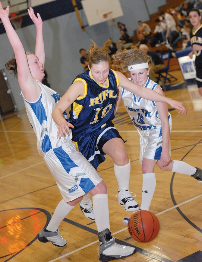 Rifle's Quincey Snyder tries to break through Moffat County's defense of Desirae Pearcey, left, and Angela Charchalis at Saturday night's game. The Bulldogs won, 37-29.