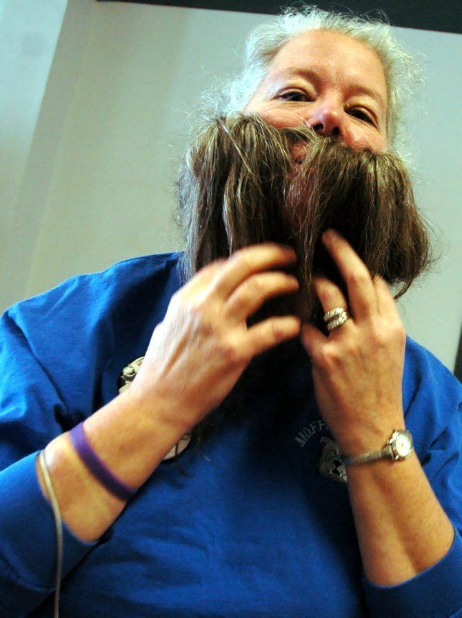 Beth Gilchrist, of the Craig Centennial committee, shows off how she can grow a beard by pulling her hair forward during a pause at Saturday's beard-growing contest signup at the Centennial Mall. The contest kicks off the Centennial celebration, and contestants are not supposed to shave for 100 days. Beards will be judged April 21, the same day Craig was incorporated 100 years ago.