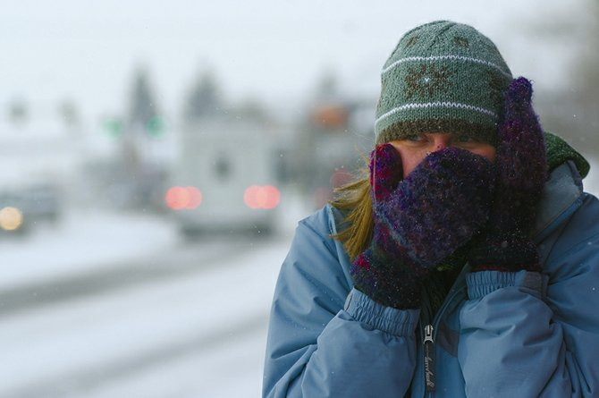 Nicole Palus, of Wisconsin, attempts to escape the frigid temperatures in Steamboat Springs on Thursday afternoon while waiting for a bus at Third Street and Lincoln Avenue.