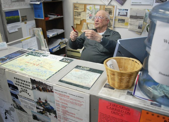 Ned Miller, former Sportsman Information Specialist at the Moffat County Visitor Center, talks with a customer Tuesday afternoon at his desk. Miller officially retired from the position but has volunteered to help at the visitor center until the Chamber of Commerce selects his replacement.