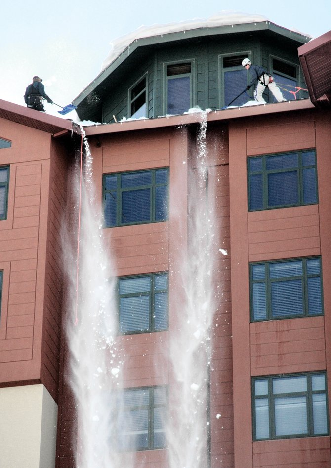 Snow removal workers clear the roof of the Steamboat Grand Resort Hotel on Tuesday afternoon.