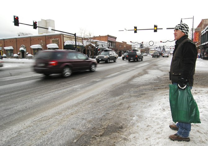 Visitor Peter Llewellyn waits to cross Lincoln Avenue on Monday afternoon after shopping at several local stores in downtown Steamboat Springs.