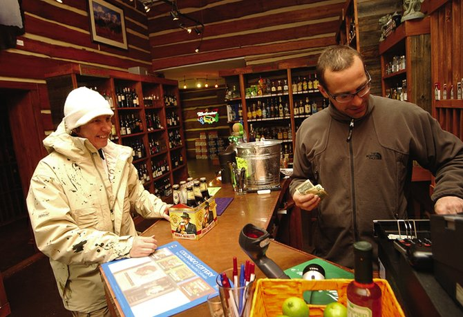 Fiona MacLeod of Scotland purchases beer Thursday afternoon from Jeff Worst, co-owner of Pioneer Spirits, 1104 Lincoln Ave. Colorado lawmakers are considering legislation that would allow liquor sales on Sundays and permit grocery stores to sell wine and beer with more than 3.2 percent alcohol content.