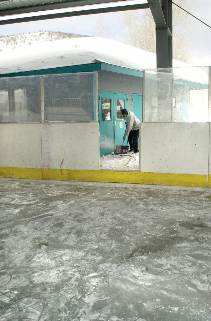 Brett Lindstrom clears snow from walkways at the hockey rink in Oak Creek in this file photo. The Oak Creek Town Board renewed its annual agreement with the Oak Creek Hockey Association at a meeting Thursday. The Town Board hopes to make improvements to the facility, including a possible full-time maintenance person.