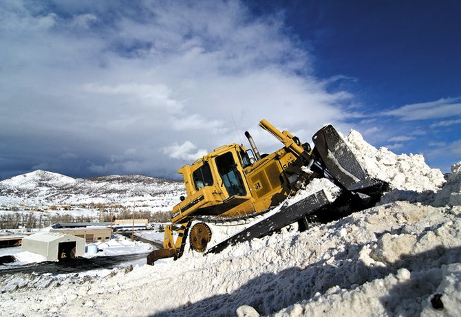 City of Steamboat Springs equipment operator Steve Meade uses a bulldozer to push snow up the mountain that's formed behind the public works shop off of Critter Court near downtown Steamboat. The city uses the area to store snow removed from city streets during the winter.