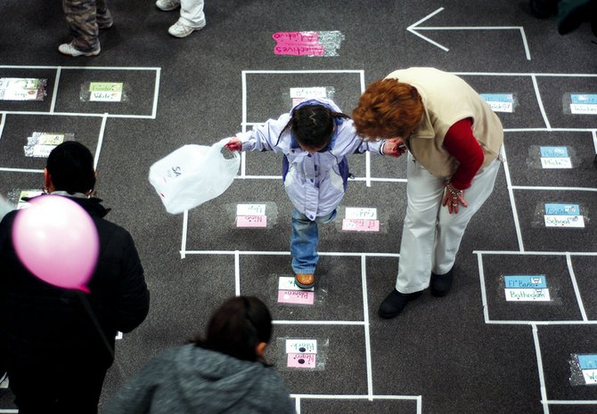 "Emma Gines, 4, plays ""literary hopscotch"" led by Martha Martinez on Thursday night at the Family Literacy Carnival, presented by the Sagebrush Reading Council at Moffat County High School. Students of all ages participated in different literary activities at the event."