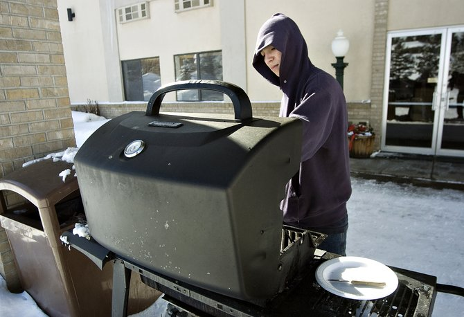 Mark Garcia grills his lunch outside the Iron Horse Inn in Steamboat Springs on Thursday afternoon. The city is seeking proposals from private firms for a management plan for the inn.