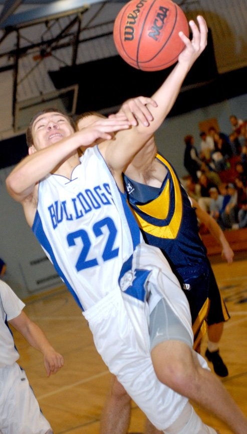 Moffat County High School's Mike Peters is fouled while shooting in an early January home game against Rifle. On Saturday, the Bulldogs lost on the road to the Bears.