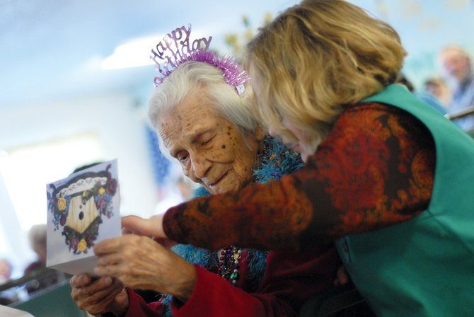 Pat Moul reads a birthday card with her great-granddaughter Emma Moul, 9, during Pat's 100th birthday celebration Tuesday at Sunset Meadows I. The card, as well as a Craig Centennial mug and coin, were given to her by Craig Mayor Don Jones.