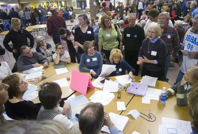 Routt County Democratic Precinct Committee Person Marlyn Myers, top right in blue turtleneck, explains the straw polling process to caucus-goers at the Steamboat Springs High School on Tuesday night.