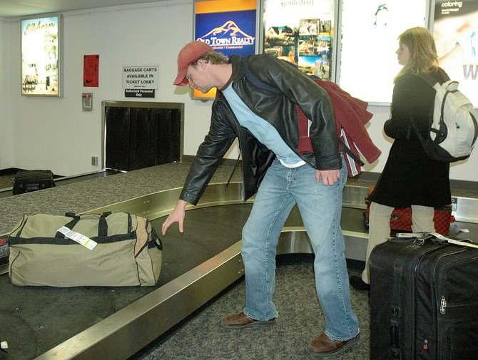 David Carr, of Baton Rouge, La., reaches for a bag at the Yampa Valley Regional Airport on  Dec. 28, 2006. Starting May 5, United Airlines will begin charging an additional fee for extra checked baggage.