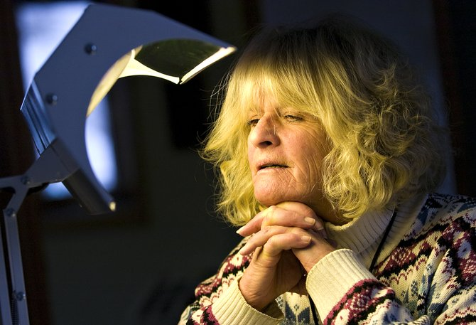 Carla Portigal demonstrates the use of a full spectrum light for treating Seasonal Affective Disorder at the Steamboat Mental Health offices Friday afternoon.