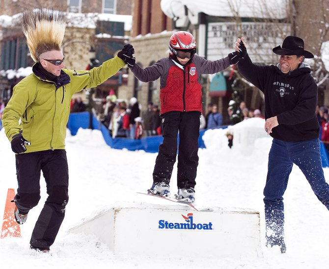 Skiing icon Glen Plake, left, and Scott Flower, right, help Cole Puckett over the jump ramp on Lincoln Avenue during Winter Carnival on Saturday.