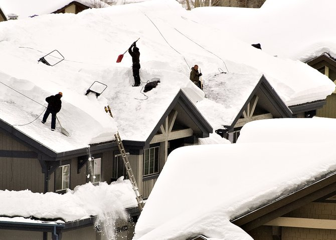A crew works to clear the snowpack from the roof of a condominium building near the Steamboat Ski Area in Steamboat Springs on Monday afternoon. As season-to-date snowfall passed the historical average of 331 inches last week, calls to snow removal businesses have increased. 