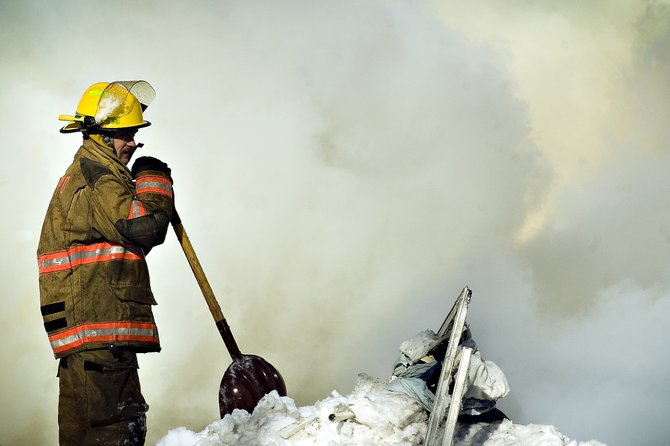 An Oak Creek Fire Protection District firefighter pauses while shoveling snow and debris from the site of a home explosion in Oak Creek on Wednesday morning. The blast and subsequent fiery collapse killed one male occupant in the house.
