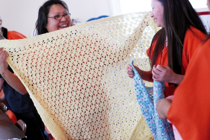 Valerie Paddy, left, shows off the blanket she crocheted to Jolene Riveis on Thursday at the Yampa Valley Pregnancy Center.  The ladies were with a group from the Moffat County Jail who all crocheted blankets to donate to the Pregnancy Center.