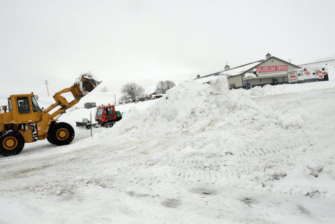Tractors move snow Thursday at the Wyman Museum in preparation for the annual Vintage Snowmobile Show and X-treme Mountain Racing.  The event begins at 9 a.m. Saturday and Sunday.