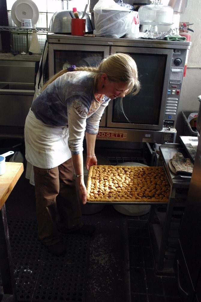 The Mugshot owner Jane Sindell puts baked goods into cooling racks at her coffeshop Friday in Oak Creek. Sindell, who plans to open a wine bar at the same location, was granted a liquor license Thursday by the Oak Creek Town Board.