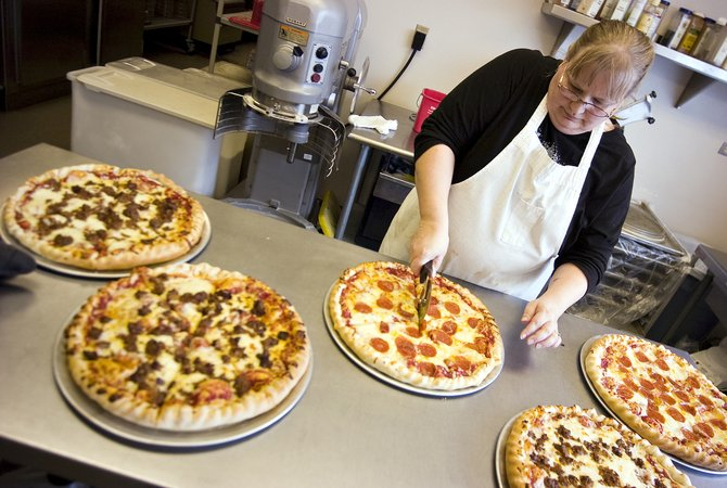 Food service employee Robin Dorr slices pizza in the kitchen at Steamboat Springs High School on Wednesday morning. The U.S. Department of Agriculture recalled 143 million pounds of beef, and about 120 pounds remain in the South Routt and Hayden school districts. The meat will be disposed of.