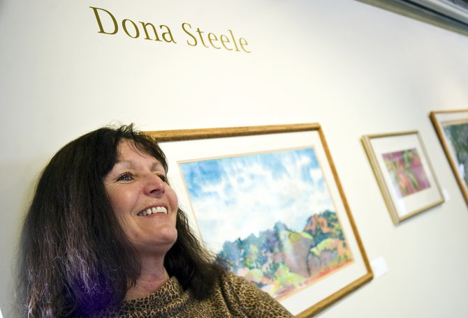 Local artist Dona Steele stands near a display of her paintings in the Emerging Artists Gallery inside the Depot Art Center in Steamboat Springs on Wednesday afternoon.