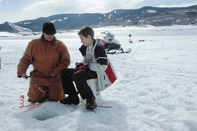 District Wildlife Manager Libbie Miller of the Division of WIldlife assists South Routt Middle School student Eric Hanes on Friday in his first ice fishing lesson. Hanes was one of 50 South Routt students who participated in Winter Studies Day.