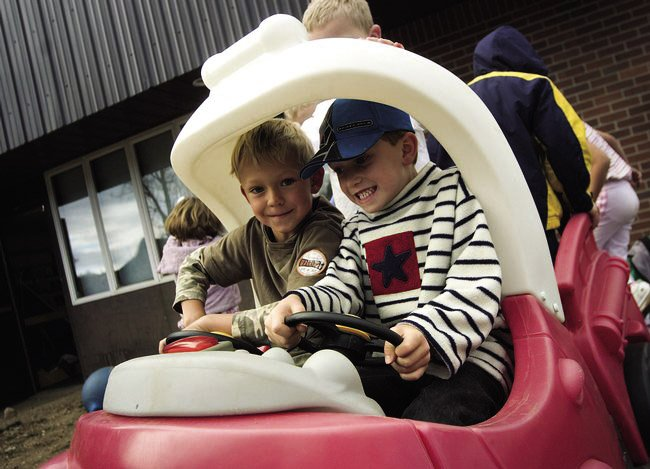 Kindergartners Jack Colfer, left, and Kevin Kaster play in a toy car on the playground at Soda Creek Elementary School in November 2007. Steamboat Springs School District officials are using an online survey to gather input on all-day kindergarten.