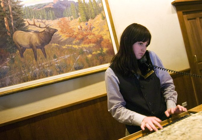 Sheraton Steamboat Resort employee Kaitlin Gallivan handles a customer inquiry on the phone at the hotel in Steamboat Springs on Thursday afternoon. The Sheraton Steamboat Resort will shut its doors two days early this ski season to begin full-scale renovations.