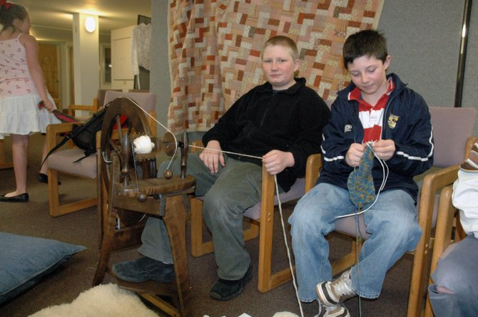 Nathan Ragan, left, and Trent Trask, both 11, spend part of their Blues Break spinning wool and learning to knit socks at the 4-H Fiber Arts Camp.