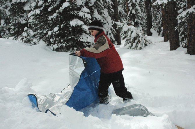 Lowell Whiteman Primary School student Dylan Parsons, 11, lays out an emergency blanket to keep firewood dry this week during an overnight excursion near Pearl Lake State Park. The school's fifth- and sixth-graders learned how to build a fire, emergency shelters and first aid skills during the annual winter skills trip. Seventh- and eighth-graders spent a night at Steamboat Lake.