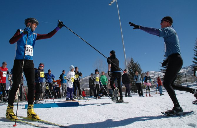 """Dan Hudspeth, left, reaches out to tag his teammate, Jim Lane, as he prepared to start the third leg of the Steamboat Pentathlon. Hudspeth and Lane formed """"Team Binge and Purge."""""""