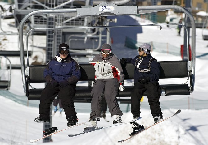 Snowboarders Kevin Anthony, from left, Bobbi Bentz and Christopher Rodriguez ride the Christie Peak Express chairlift on Wednesday morning. Anthony and Rodriguez visited Steamboat Springs this week with the Sunshine Kids Foundation.
