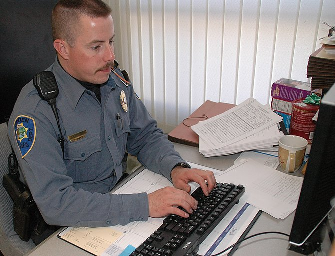 Hayden Police Officer Ed Corriveau works in his office Wednesday. Hayden residents met with officers Tuesday night to air grievances about local police.