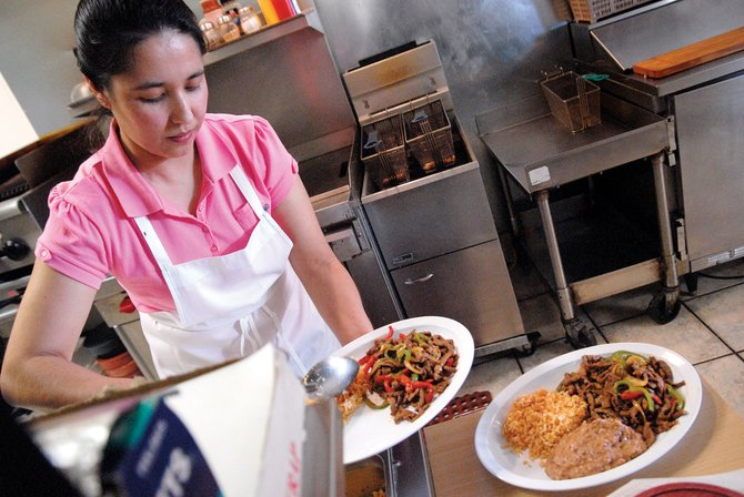 "Blanca Loya fixes two plates of ""Carne Mexicana"" at El Ranchero restaurant, 337 W. Victory Way. The food at the restaurant is the same she makes at home, she said."