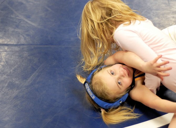Dezzee Pfister, 5, looks up as she is pinned by Katelynn Baker, 6, on Thursday at Moffat County High School during practice for Bad Dogs youth wrestling.  Pfister wrestles in the six-and-younger category, while Baker was helping out because she has two brothers also on the team.