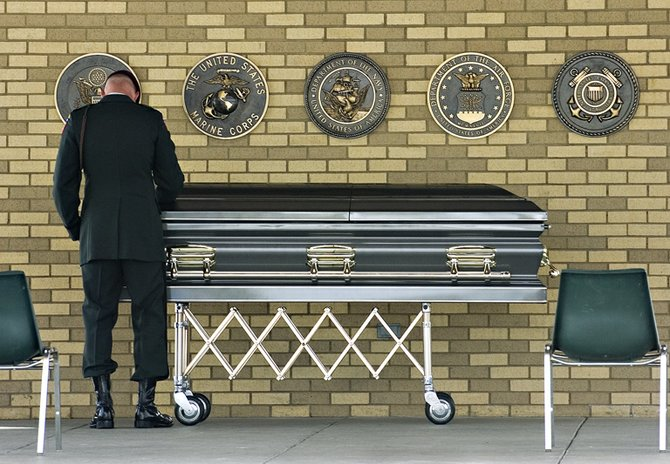 A member of the honor guard pays his respects near the casket of Eric O'Hara at Fort Logan National Cemetery in Denver on Thursday afternoon.