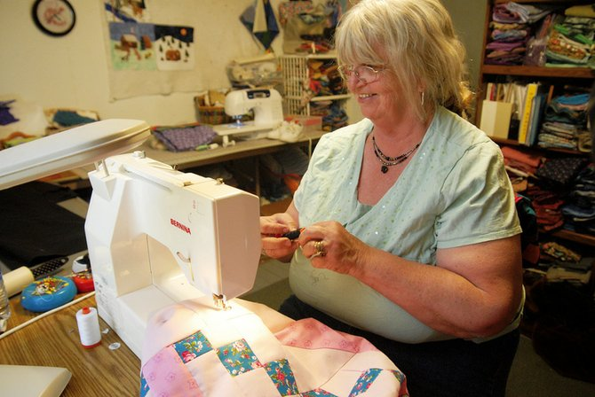 Linda Pinnt quilts one of the pink quilts Wednesday in her home. Pinnt has been quilting for about 20 years and started making the pink quilts last year when her son's companion found out she had cancer.