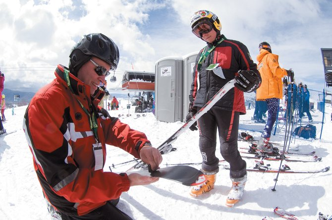 Eleven-year-old Alex Stojda watches as his father Mike fine-tunes his skis prior to Friday's race at the NASTAR National Championships at Steamboat Ski Area. The races drew 1,100 athletes to Steamboat Springs looking for national titles.