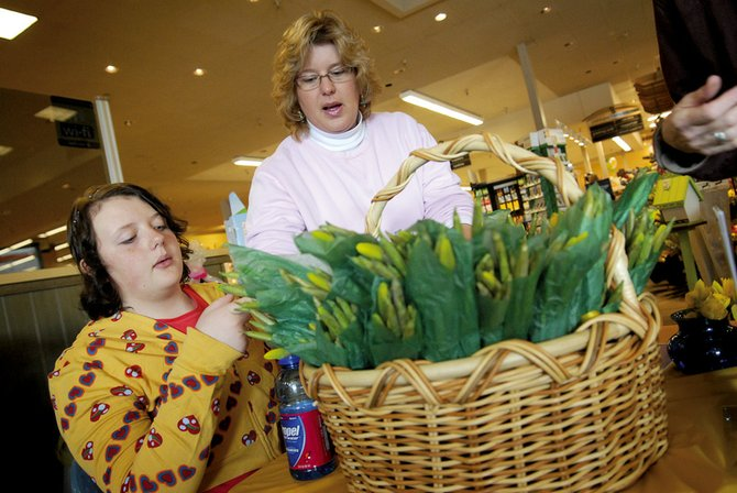 "Megan, left, and Melody Gingrich pick out some choice daffodils for a customer Tuesday at Safeway in Craig. The pair was among a number of volunteers selling daffodils called ""Heralds of Hope"" at Safeway, City Market, The Flower Mine and the Northwest Colorado Visiting Nurse Association's Craig office as a fundraiser for hospice care. The fundraiser went on throughout the day."