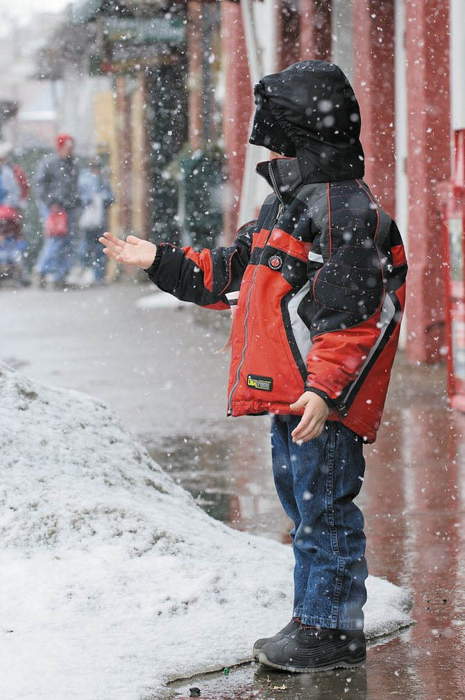 Elijah Gerhard checks out the snow falling in downtown Steamboat Springs on Thursday afternoon. Gerhard and his family are visiting Steamboat Springs from Plano, Texas. The National Weather Service forecast several inches of snow overnight Thursday, potentially enough for the Steamboat Ski Area to break its single-season snowfall record.