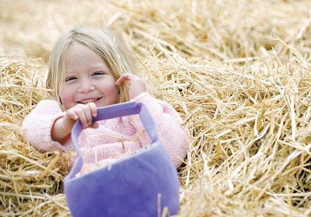 Makayla Suriano-Husman takes a break from searching for eggs to roll in the hay during the 32nd Annual Egg Hunt on April 7, 2007, at Howelsen Hill. The children searched for eggs and also had a chance to meet the Easter Bunny, who arrived via the Barrows Chairlift down Howelsen Hill.