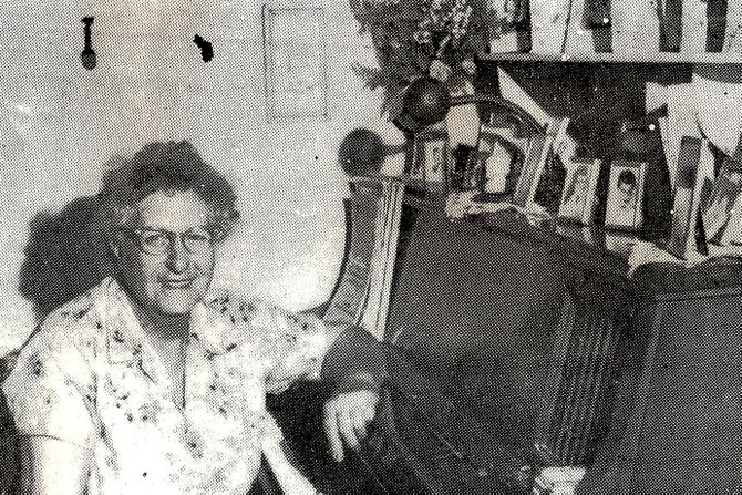 "Emmy Wehrlin poses at her piano-organ with what she called her ""Gallery of Fame,"" pictures of some of the students she taught throughout the years."