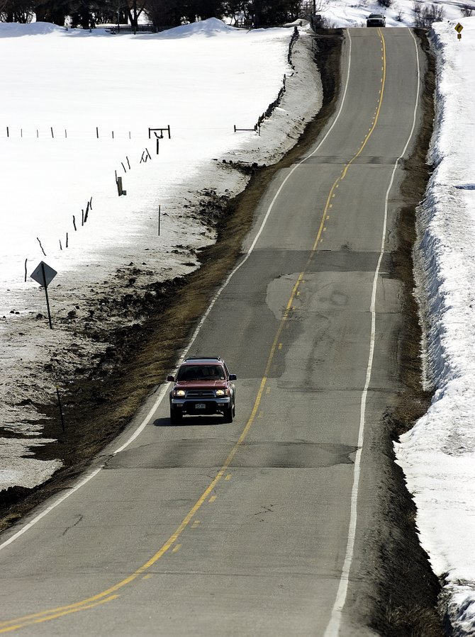 A motorist makes his way over a patched section of Routt County Road 14 outside of Steamboat Springs on Monday afternoon. County officials are hosting an open meeting today regarding potential county road improvements.