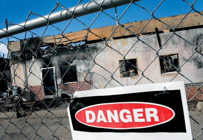 A reward has been issued for information about the Country Mall fire, which occurred late last year. Danger signs around the ashen building lets onlookers know of asbestos issues in the remains.