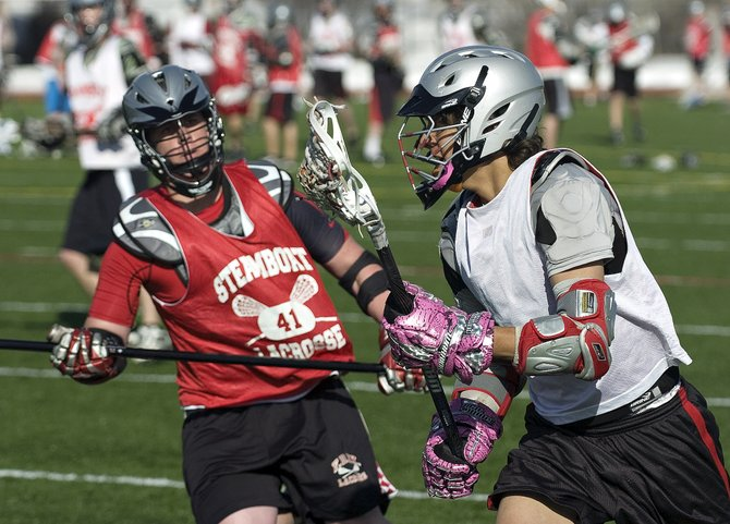 Chase Grippa, right, looks past defender Joe Nerney during the Steamboat Springs High School lacrosse team's practice at Gardner Field on Tuesday afternoon.